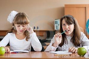 two-girls-sitting-school-desk-10627937